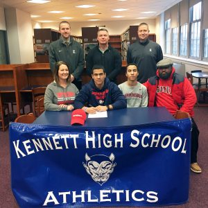 Student-Athlete signing letter of intent surrounded by parents and coaches