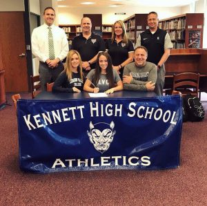 group photo showing student athlete signing papers