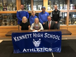 Young woman sitting with parents and coaches surrounding her.